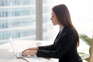 Successful serious business lady working at office desk using la